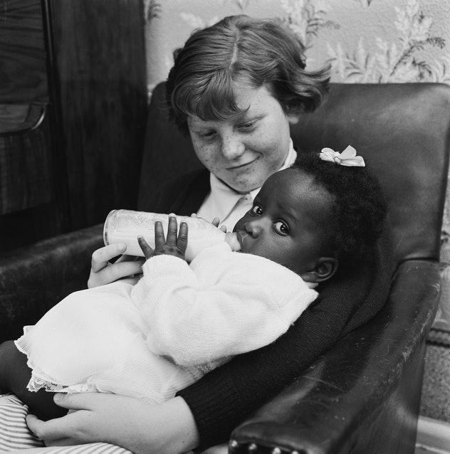 The mixed race Long family of Olyffe Avenue in Welling, Kent, July 1960. Twelve-year-old Joan helps feed her adopted sister, baby Kim. (Photo by Frank Martin/BIPS/Hulton Archive/Getty Images)