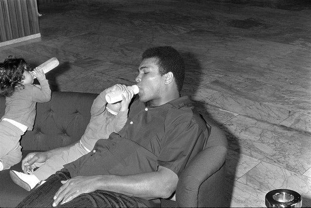Muhammad Ali drinks from the baby botlle of his daughter, Zurich 1971   (Photo by Blick Sport/RDB/ullstein bild via Getty Images)