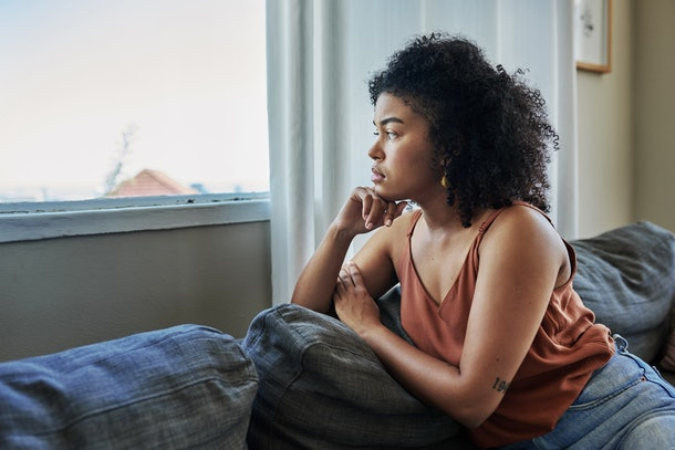 Shot of a young woman looking pensively out a window at home