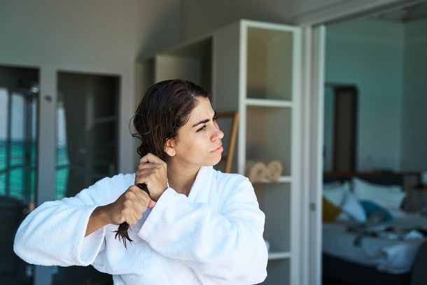 Content young female wearing white bathrobe squeezing wet hair gently after taking shower in modern apartment and looking away