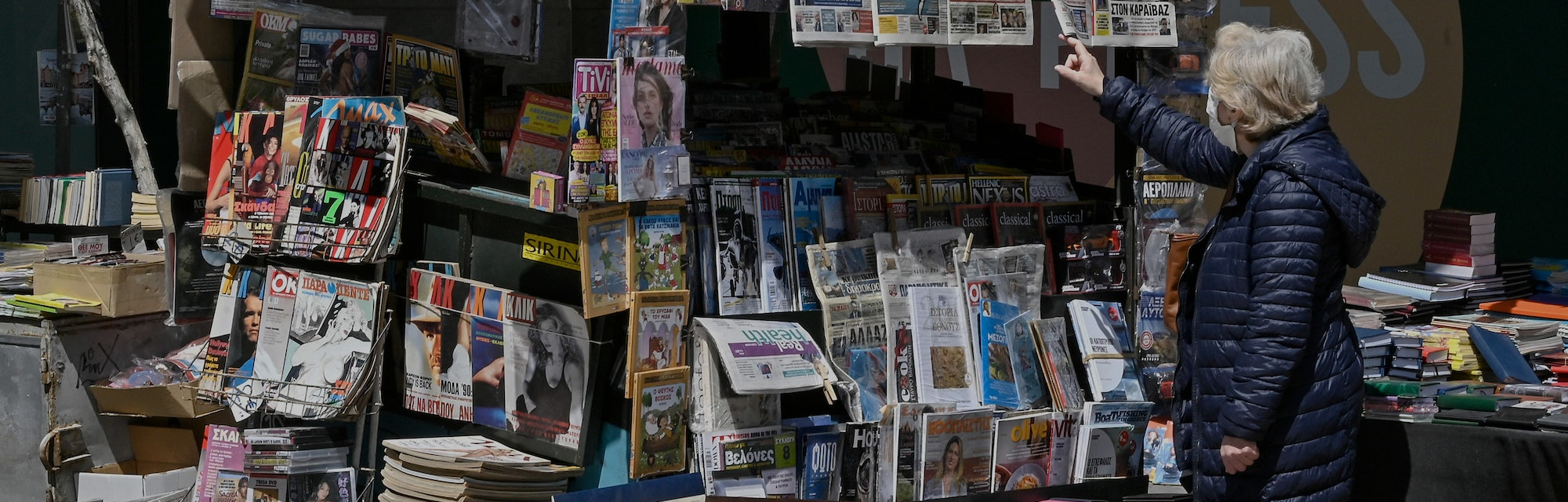 A woman reads newspaper's headlines referring to the killing of a Greek journalist in Athens on Apri...