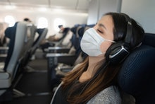 Portrait of a Latin American woman traveling by plane wearing a facemask and sleeping onboard