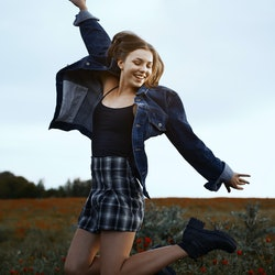 Young teen girl jumping in a field of red poppies