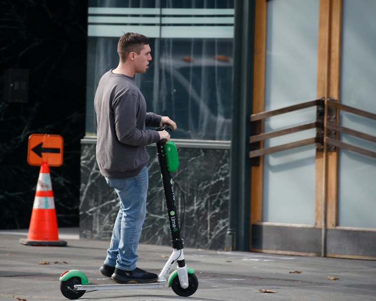 OAKLAND, CA: JANUARY 07: A man rides a Lime scooter on the sidewalk near Broadway in Oakland, Calif., on Tuesday, Jan. 7 2020. The number of nationwide hospital admissions from scooter accidents increased by 365% between 2014 and 2018, according to a team of San Francisco trauma specialists and researchers. (Jane Tyska/Digital First Media/East Bay Times via Getty Images)