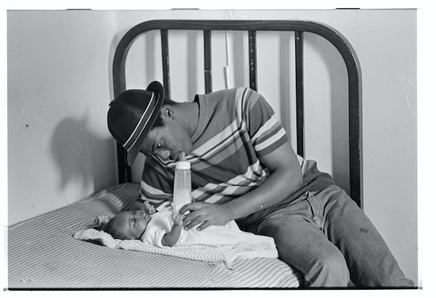 Father Sitting on Bed with Infant   (Photo by David Turnley/Corbis/VCG via Getty Images)