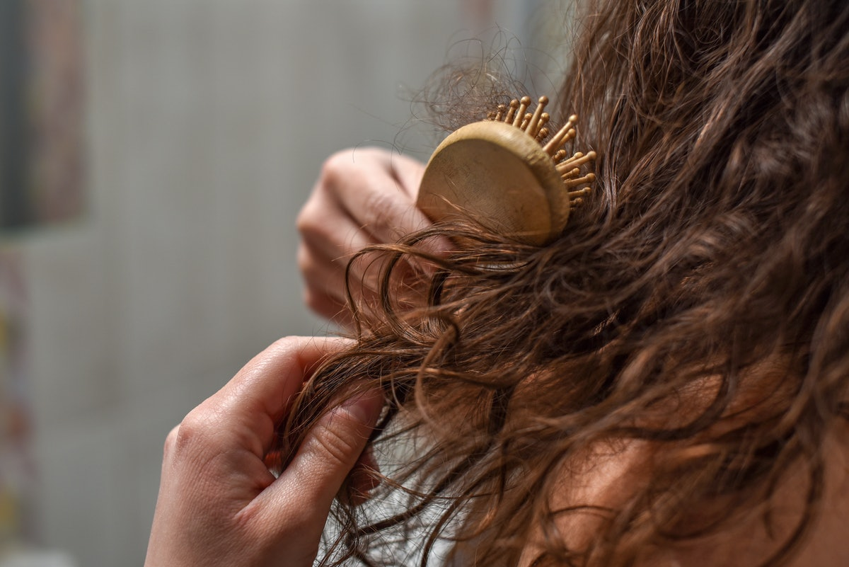 Young Upset Woman In Bathroom Holding Brush With Hair , Hair Loss And Hair Care Concept