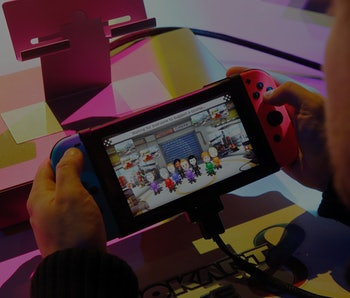 "PARIS, FRANCE - JANUARY 13:  A visitor plays the ""Mario Kart 8 Deluxe"" video game on a Nintendo Switch games console during the new console's unveiling by Nintendo Co on January 13, 2017 in Paris, France. This next-generation game console, billed as a combination of a home device experience and a portable entertainment system, will be available for $ 299.99 in the US from March.  (Photo by Chesnot/Getty Images)"
