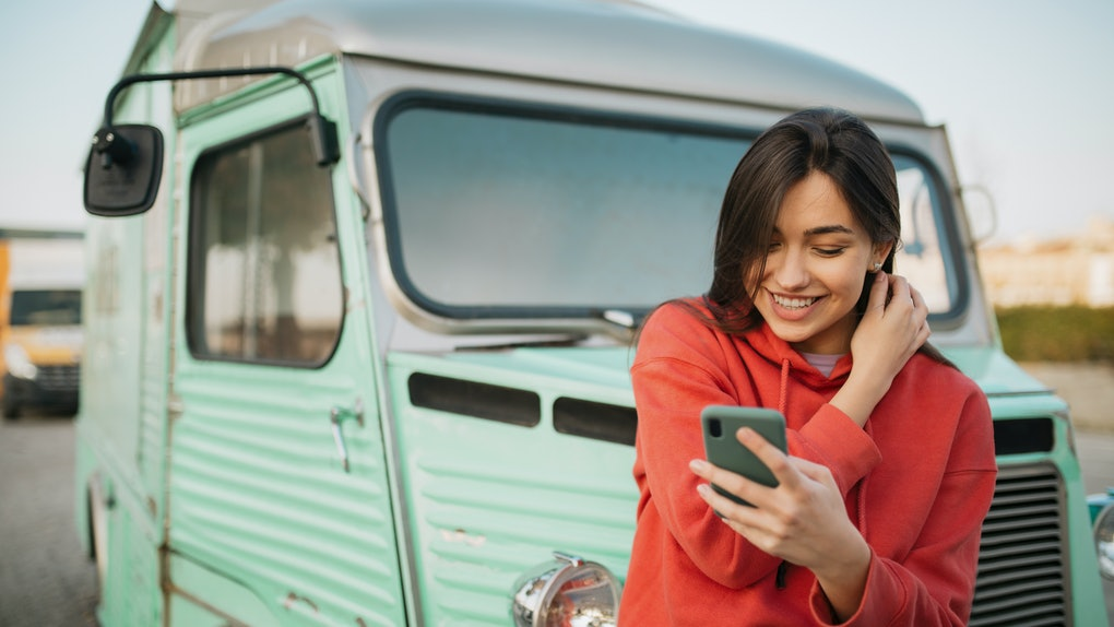 Happy young Caucasian woman standing outdoors, in front of an old truck and in a red shirt, smiling and using a smart phone