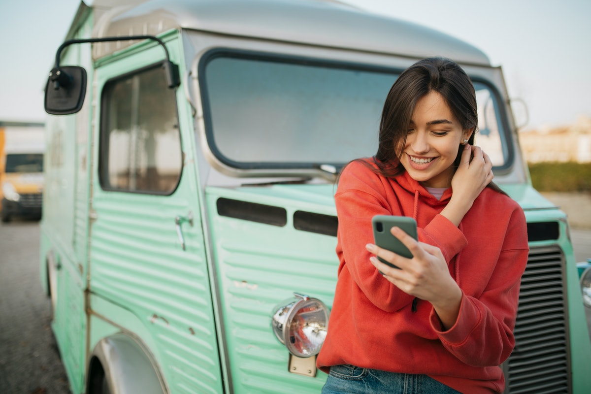 Happy young Caucasian woman standing outdoors, in front of an old truck and in a red shirt, smiling ...