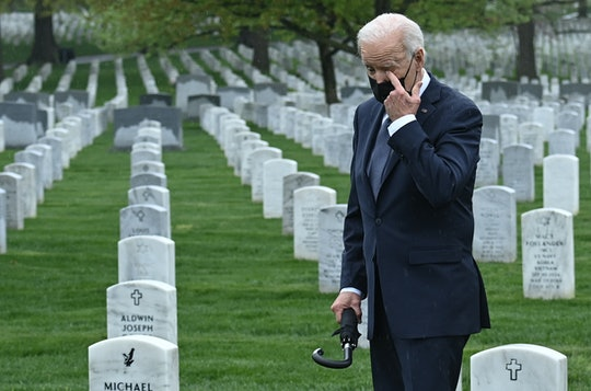 """US President Joe Biden wipes his eye as he walks through Arlington National cemetary to honor fallen veterans of the Afghan conflict in Arlington, Virginia on April 14, 2021. - President Joe Biden announced it's """"time to end"""" America's longest war with the unconditional withdrawal of troops from Afghanistan, where they have spent two decades in a bloody, largely fruitless battle against the Taliban. (Photo by Brendan SMIALOWSKI / AFP) (Photo by BRENDAN SMIALOWSKI/AFP via Getty Images)"""