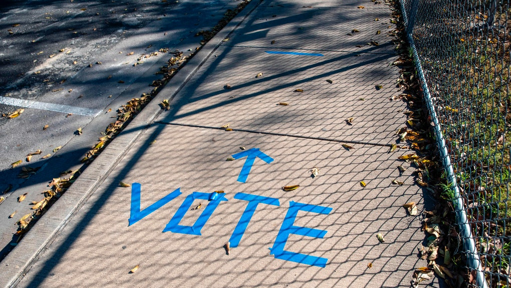"A sidewalk is shown with ""Vote"" written in tape outside a polling location on election dayy in Austin, Texas on November 3, 2020. - Americans were voting on Tuesday under the shadow of a surging coronavirus pandemic to decide whether to reelect Republican Donald Trump, one of the most polarizing presidents in US history, or send Democrat Joe Biden to the White House. (Photo by Sergio Flores / AFP) (Photo by SERGIO FLORES/AFP via Getty Images)"