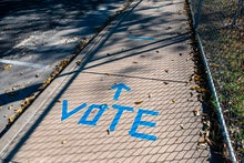 """A sidewalk is shown with """"Vote"""" written in tape outside a polling location on election dayy in Austi..."""