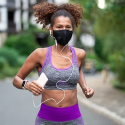 A person wearing a gray and purple sports bra, headphones, and a mask runs outside. As long as you're feeling up to it, you can work out both before and after getting your COVID vaccine.