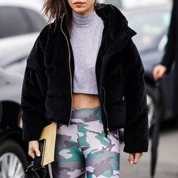 PARIS, FRANCE - FEBRUARY 28: A guest wears sunglasses, a black coat with fluffy parts, a gray wool turtleneck crop top, military camouflage pattern printed gray and green leggings, a leather bag, outside Balmain, during Paris Fashion Week - Womenswear Fall/Winter 2020/2021, on February 28, 2020 in Paris, France. (Photo by Edward Berthelot/Getty Images)