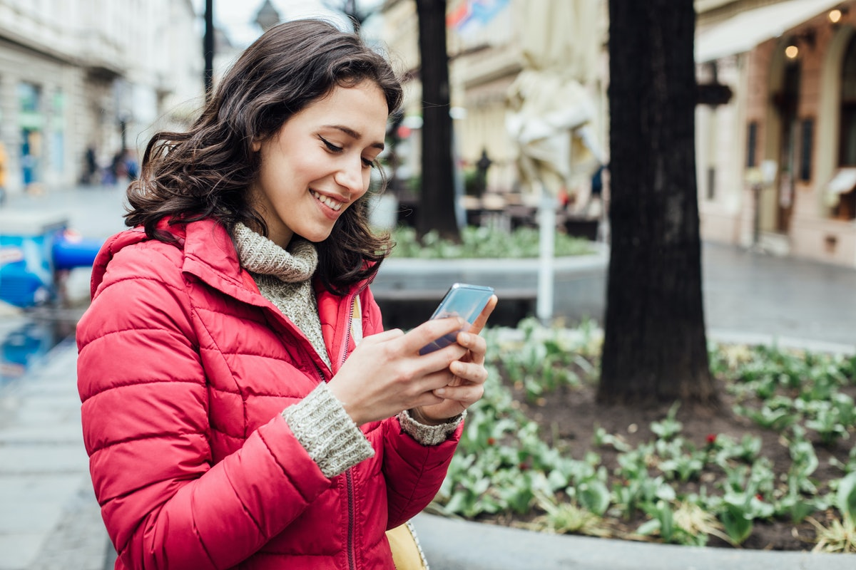 Portrait of a beautiful young woman using her smartphone in the city.