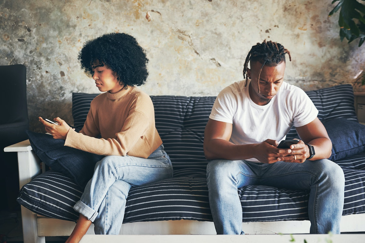 Shot of a young couple using their cellphones at home