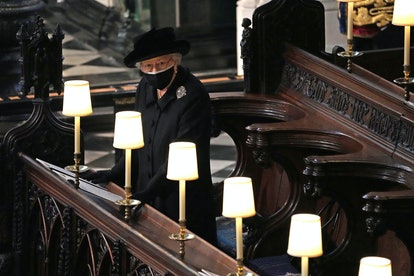 Queen Elizabeth II watches as pallbearers carry the coffin of Britain's Prince Philip, Duke of Edinburgh during his funeral inside St George's Chapel in Windsor Castle in Windsor, west of London, on April 17, 2021. - Philip, who was married to Queen Elizabeth II for 73 years, died on April 9 aged 99 just weeks after a month-long stay in hospital for treatment to a heart condition and an infection. (Photo by Yui Mok / POOL / AFP) (Photo by YUI MOK/POOL/AFP via Getty Images)