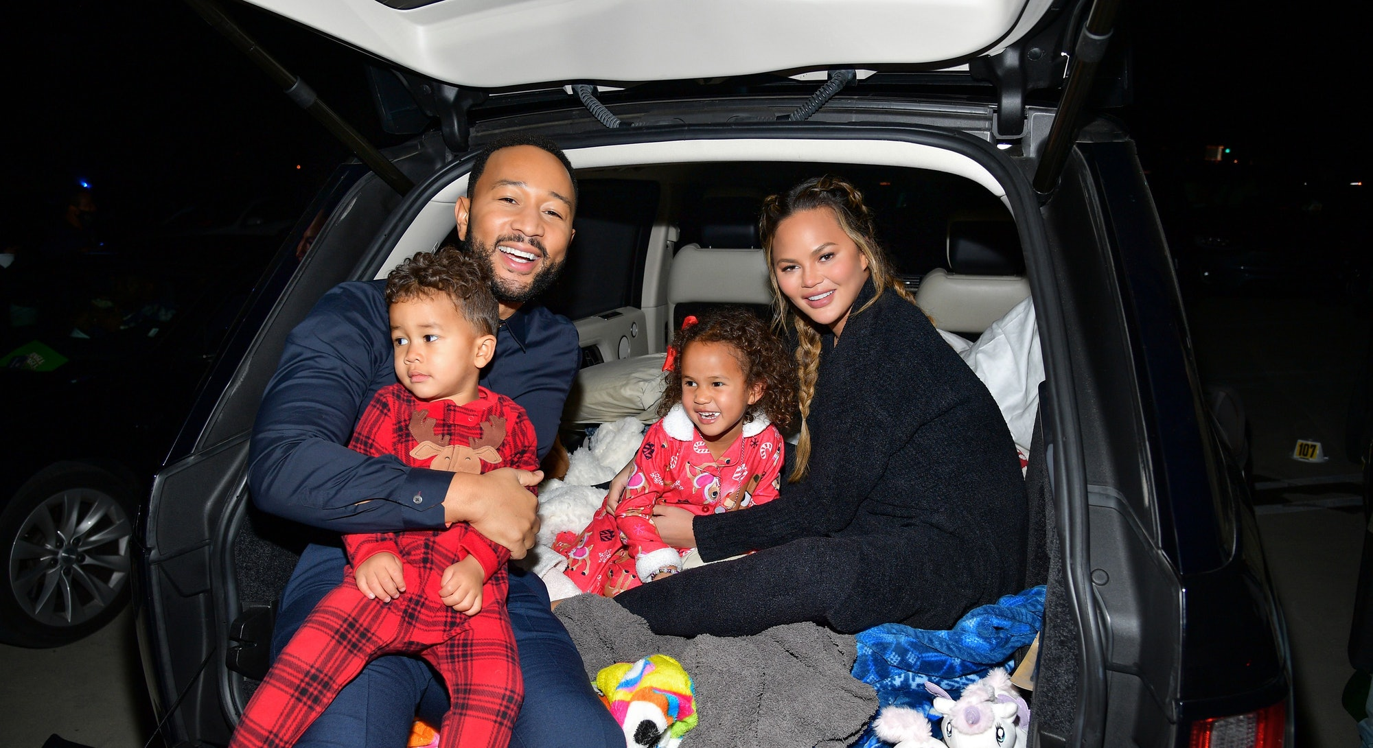 """LOS ANGELES, CALIFORNIA - NOVEMBER 13: (EDITORS NOTE: This image has been retouched) (L-R) Miles Theodore Stephens, John Legend, Luna Simone Stephens, and Chrissy Teigen attend Netflix's """"Jingle Jangle: A Christmas Journey"""" drive-in premiere at The Grove on November 13, 2020 in Los Angeles, California. (Photo by Matt Winkelmeyer/Getty Images for Netflix)"""