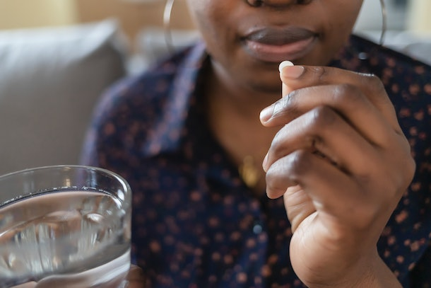 Young African American Woman Taking Pill, Supplements or Antibiotic, Female Preparing to Take Emergency Medicine, Chronic Disease, Healthcare and Treatment Concept. Closeup