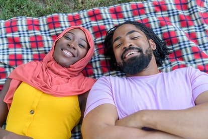 A Man and his Lovely Wife of Muslim Ethnicity are Laying on Blanket in Park and Spending a Wonderful...