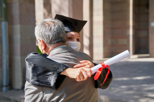 Cheerful father and graduating daughter hugging outdoor, study achievement, education
