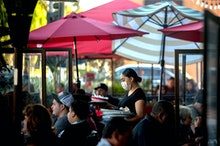 REDLANDS, CA - DECEMBER 05: A server clears a table as patrons dine outdoors at Gloria's Cocina Mexi...