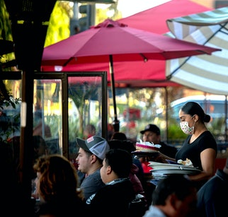 REDLANDS, CA - DECEMBER 05: A server clears a table as patrons dine outdoors at Gloria's Cocina Mexicana restaurant in Ontario on Saturday, Dec. 5, 2020. As coronavirus cases surge at a record pace, California Gov. Gavin Newsom announced a new stay-at-home order.  Restaurants will shutdown dine-in services starting Dec. 6. (Photo by Watchara Phomicinda/MediaNews Group/The Press-Enterprise via Getty Images)