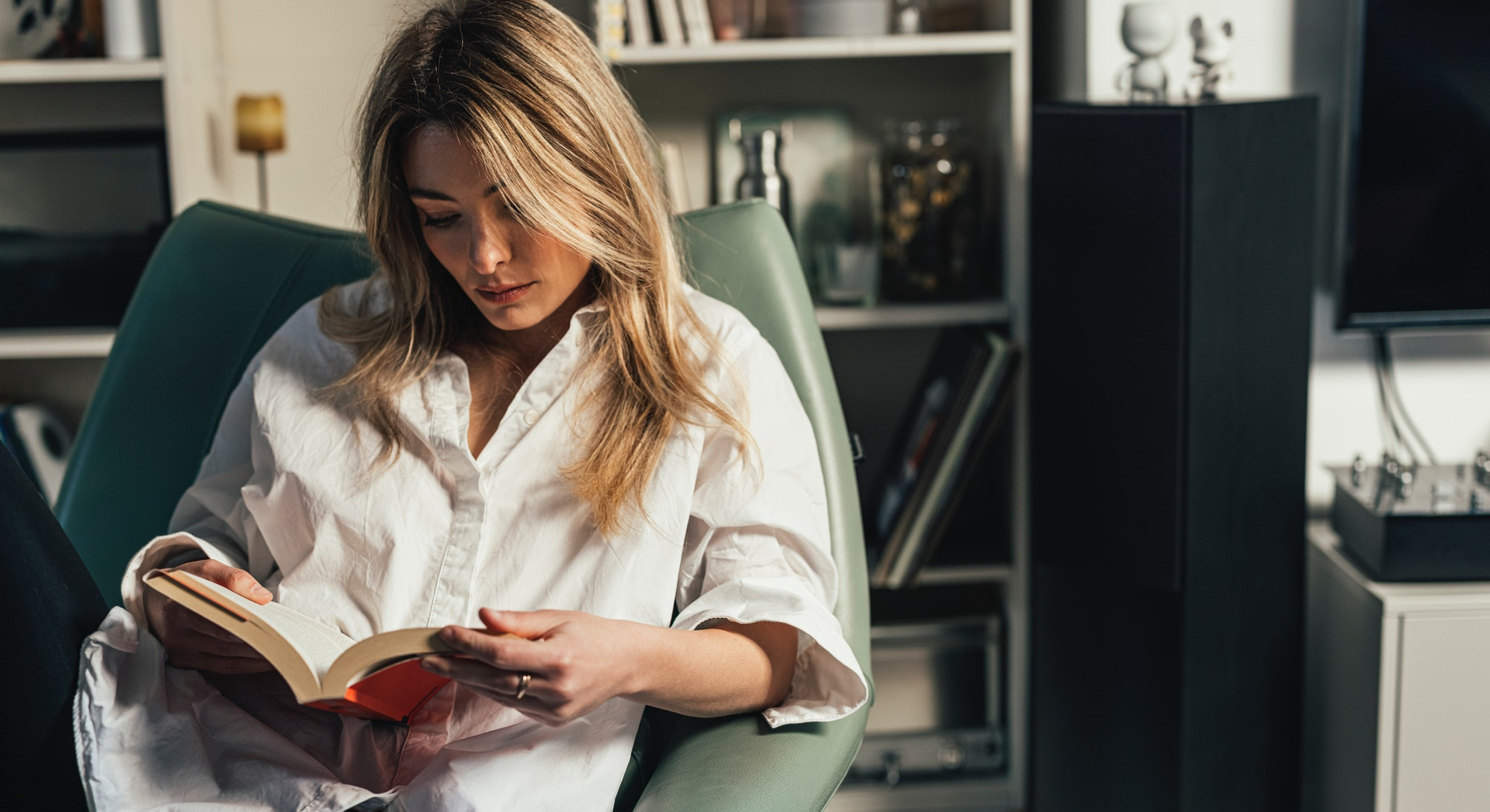 Blond elegant woman in a white shirt sitting casually in her library, reading her favorite poetry bo...