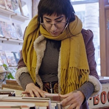 A young Latina woman with piercings and tattoos browsing through a box of books in a used bookstore.