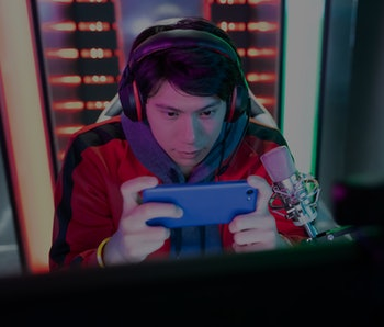 Young Asian Handsome Pro Gamer wearing headset is playing online mobile game and having live stream