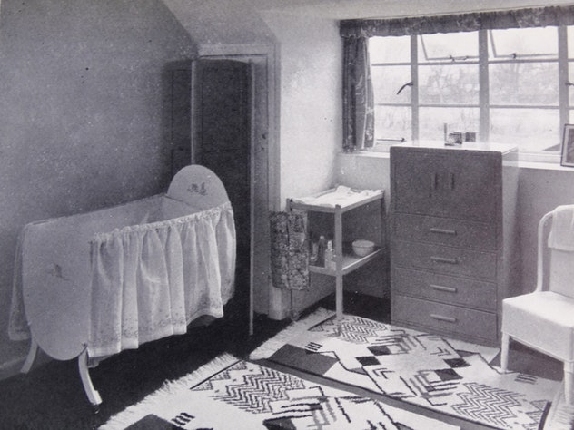 A small nursery with rugs.