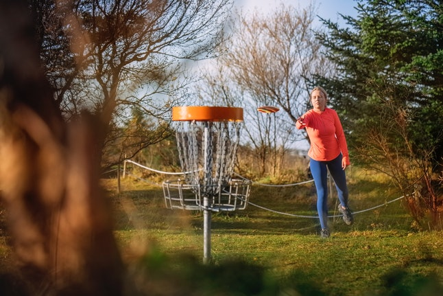 Woman tossing a disc into the basket goal. Caucasian woman playing disc golf game outdoors in a park.