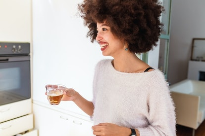 A smiling woman drinks beer. Post-COVID vaccine you should alcohol for up to 72 hours.