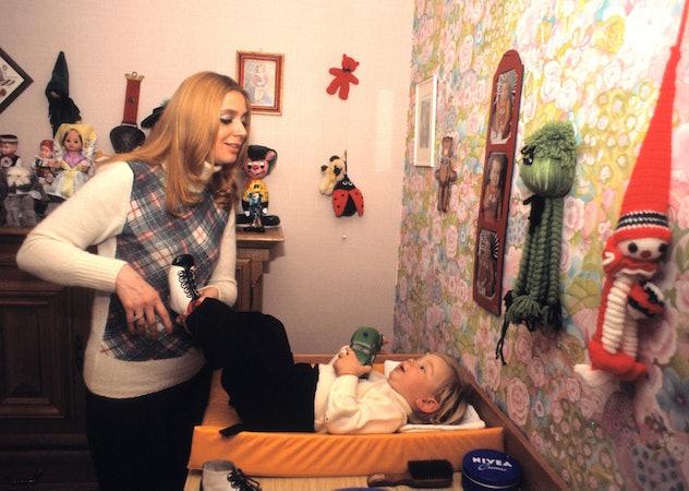 German singer Cindy Berger changes her child in his nursery.