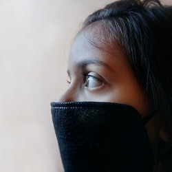 A woman wears a full COVID mask. A mask covering both nose and mouth is recommended for COVID protection.