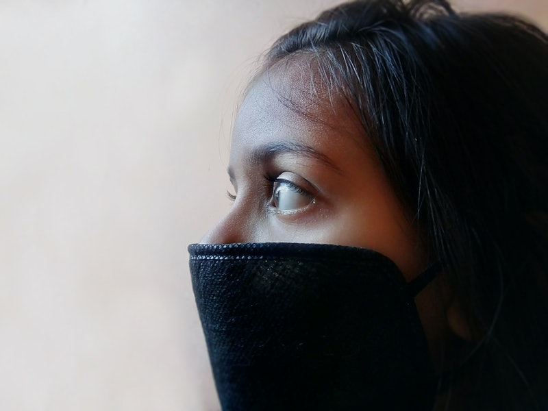 A woman wears a full COVID mask. A mask covering both nose and mouth is recommended for COVID protec...