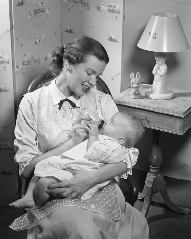 Mother gives baby a bottle in the nursery.