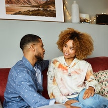Girlfriend looking at boyfriend talking while sitting on sofa. Young man and woman are discussing in...