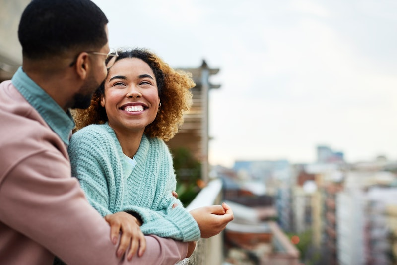 Cheerful Afro woman looking at boyfriend while spending leisure time. Happy couple is at building te...