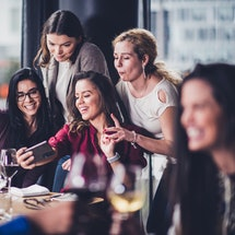 Young friends taking selfies at a restaurant. Here's how to rebuild your social interaction skills after COVID.