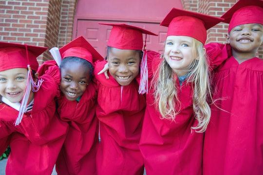 Adorable kindergarten graduates smile and pose for photo together outside preschool