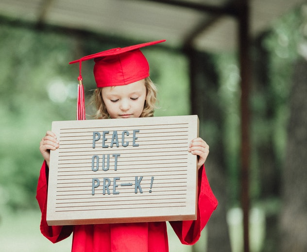 Preschool girl wearing cap and gown and holding sign