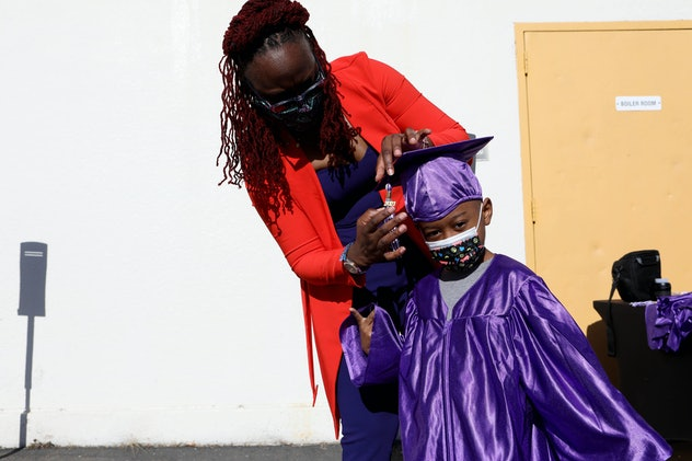 OAKLAND, CA - MARCH 26: Shaione Simmons, a transitional kindergarten and kindergarten teacher, adjusts a tassel on a graduation cap worn by kindergartener Lyndon Lumpkin, 5, prior to taking his school photo at Madison Park Academy Primary on Friday, March 26, 2021, in Oakland, Calif. The school is preparing to reopen on March 30. (Yalonda M. James/The San Francisco Chronicle via Getty Images)