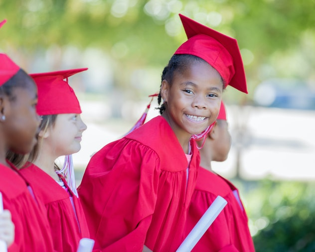 Adorable elementary age child wearing graduation cap and gown smiles during ceremony