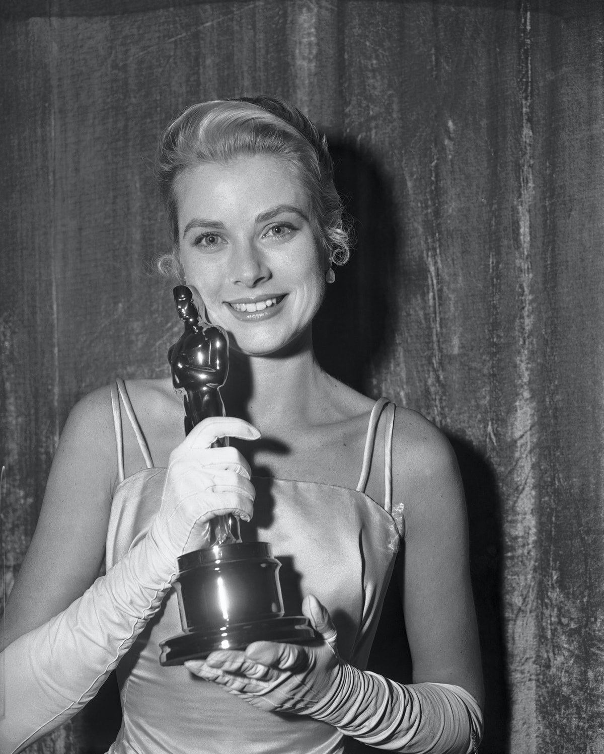 (Original Caption) Pride and Some Mutual Admiration. Hollywood, Los Angeles, California: At left above is a close up of actress Grace Kelly hugging her Oscar after she was honored as the best actress of 1954 at the 27th Academy Awards. She won the prize for her role in The Country Girl. At right, Oscar winning Kelly is kissed by Oscar winner Marlon Brando, who got the Oscar as the best actor for his role in On the Waterfront.
