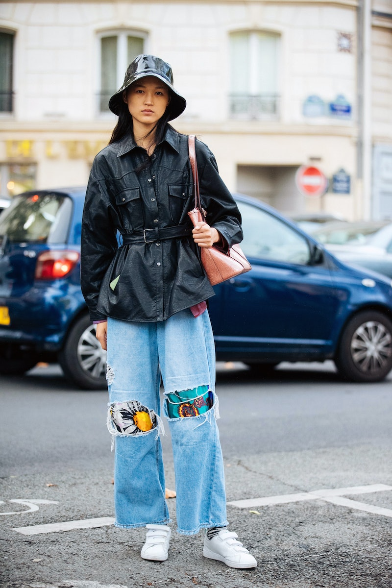 PARIS, FRANCE - SEPTEMBER 29:  Model Guannan Cai weasr a black rain/bucket hat, black leather jacket with a belt, jeans with printed patches, and white velcro sneakers after the Valentino show during Paris Fashion Week Spring/Summer 2020 on September 29, 2019 in Paris, France. (Photo by Melodie Jeng/Getty Images)