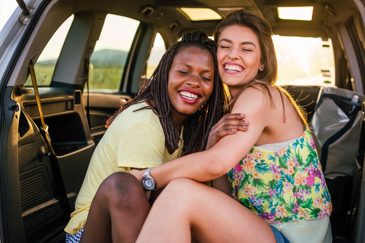 Two females, different nationalities, sitting embraced in the back of the car. They are smiling with their eyes closed.