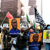 """People hold placards as they protest outside of the Courthouse during the trial of former Minneapolis police officer charged with murdering George Floyd in Minneapolis, Minnesota on April 19, 2021. - Jurors on Monday began mulling the fate of the white ex-Minneapolis policeman accused of killing African-American George Floyd, a death that sparked a nationwide reckoning on racism and which prosecutors called a """"shocking abuse of authority"""". (Photo by CHANDAN KHANNA / AFP) (Photo by CHANDAN KHANNA/AFP via Getty Images)"""