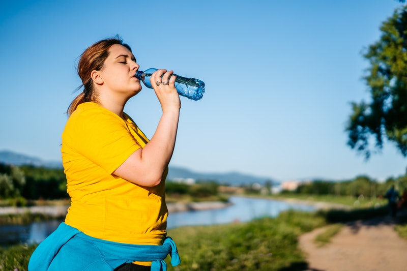 Oversized young Caucasian woman drinking water after running in a public park.