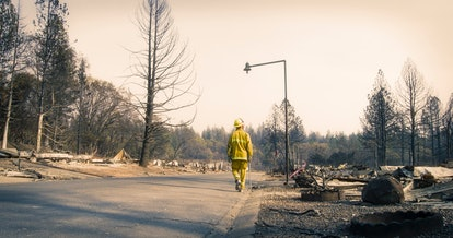 Alone on an empty street, one firefighter surveys the damage in a neighborhood where every home burn...